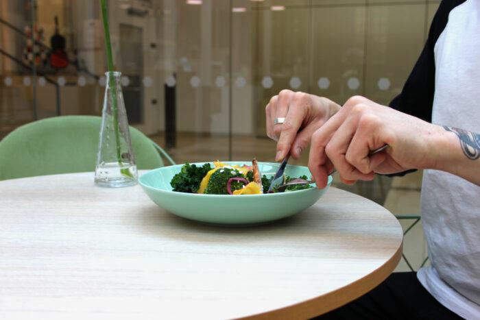 Lunchgäst i Café & Bistro. Närbild på händer.