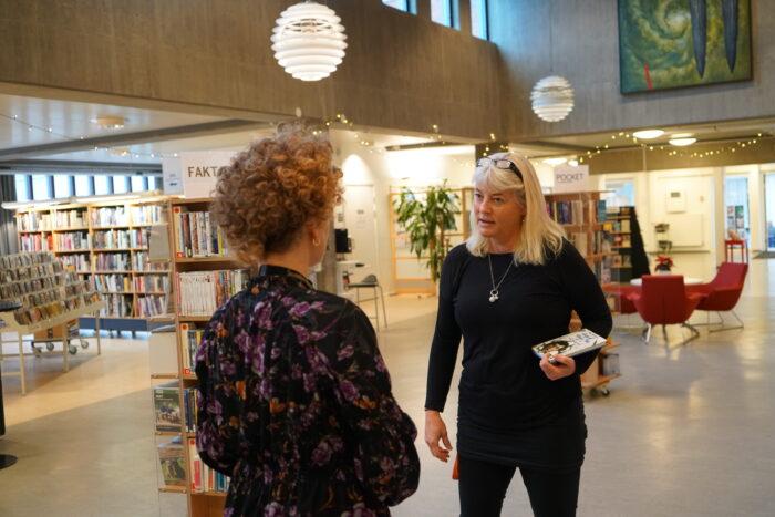 Två personer samtalar inne på Kristianstad Stadsbiblioteket