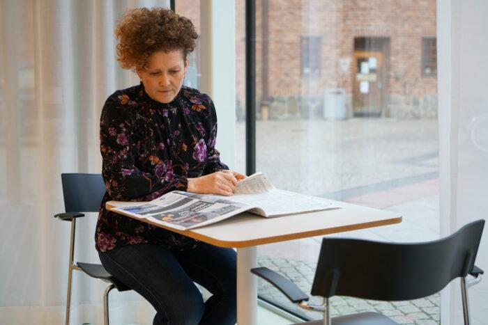 En person läser tidningen inne i Stadsbibliotekets tidningsrum